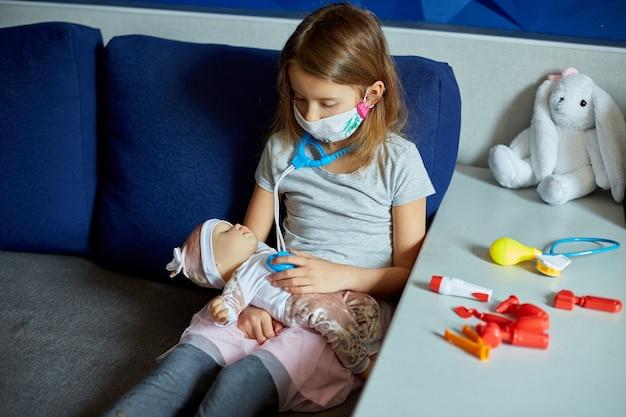 Een klein meisje met een medisch masker zit op de bank, speelt een dokter, behandelt en luistert naar de pop met een stethoscoop in een medisch masker, thuis tijdens quarantaine en pandemie