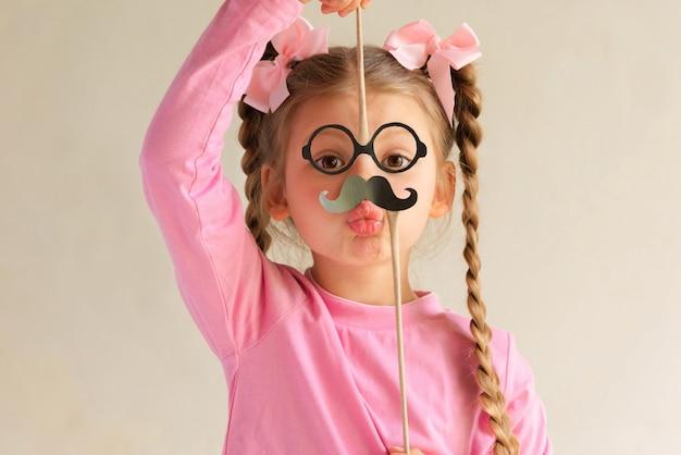 Een klein meisje met een papieren snor trekt een gezicht.