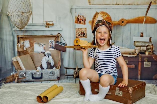 Een klein meisje met een pet zit op een retro koffer en heeft een houten vliegtuig in haar hand