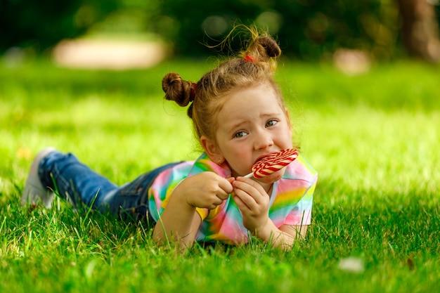 Een klein meisje met een rode lolly ligt op het zomergras in het park.