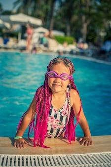 Een klein meisje met een roze zwembril gekleed in een zwempak springt uit het zwembad