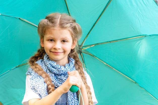 Een klein meisje met een sjaal die een paraplu vasthoudt.