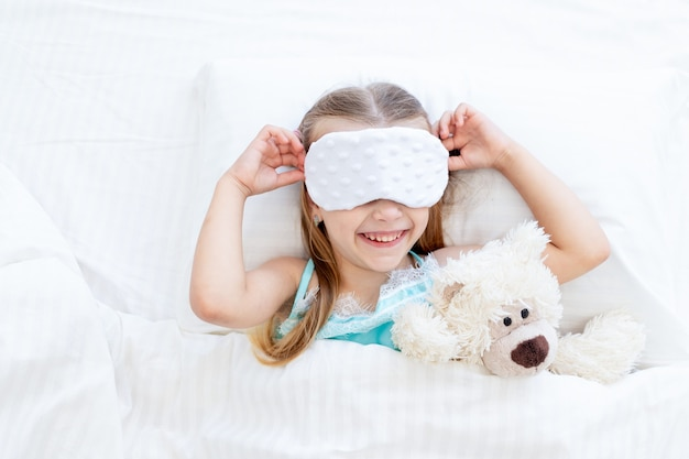 Een klein meisje met een slaapmasker werd 's ochtends thuis wakker op een bed op een wit katoenen bed met een teddybeer en een schattige glimlach