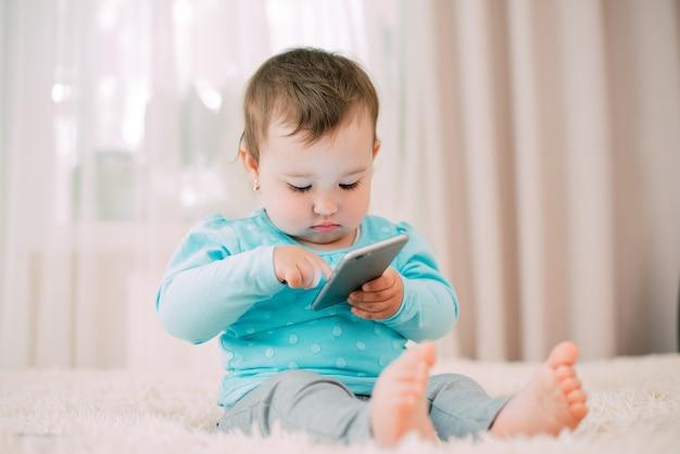 Een klein meisje met een smartphonetelefoon in haar handen zit en drukt op