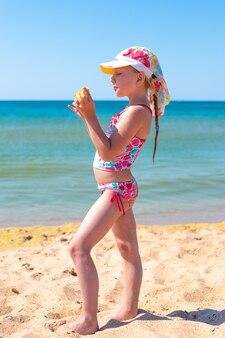 Een klein meisje met een staartje in een panama-hoed staat aan de kust en eet maïs. vakantie op zee