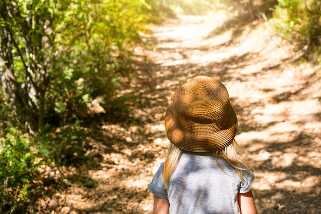 Een klein meisje met een strohoed loopt over een pad in het bos