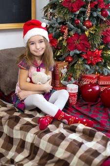Een klein meisje met een teddybeer, zittend op een geruite deken in de kerstversiering bij een kerstboom met dozen met geschenken en een kerstmuts. nieuwjaar, kinderspel
