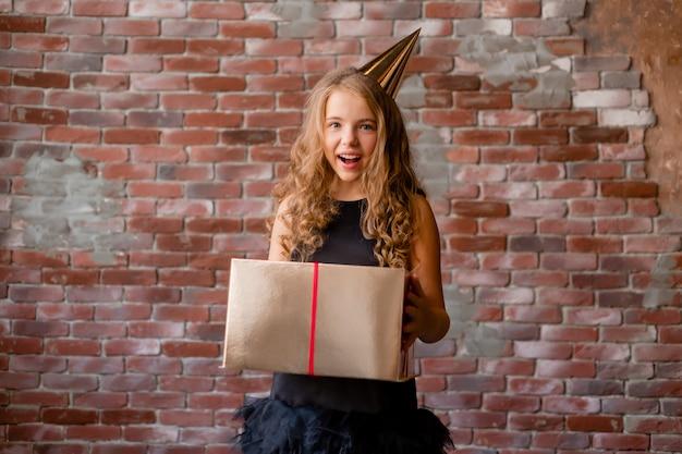 Een klein meisje met een verjaardagspet houdt een gouden geschenkdoos vast en verheugt zich.