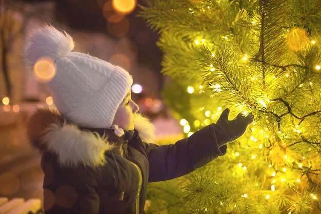 Een klein meisje met een warme muts kijkt naar de gouden lichtjes van de slingers aan de kerstboom op straat