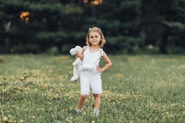 Een klein meisje met een witte beer in de openluchtmijn bij zonsondergang
