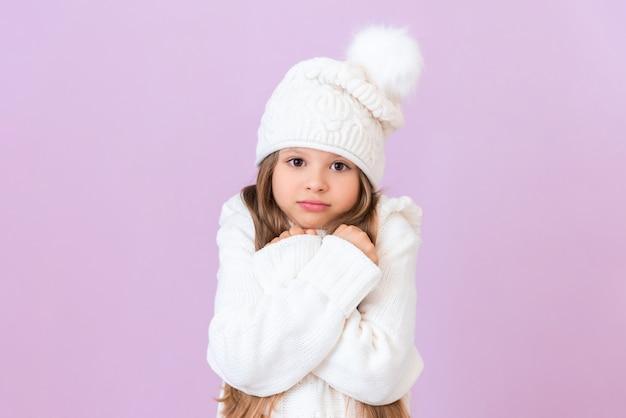 Een klein meisje met een witte wintermuts en trui heeft haar handen ingedrukt en probeert warm te blijven.