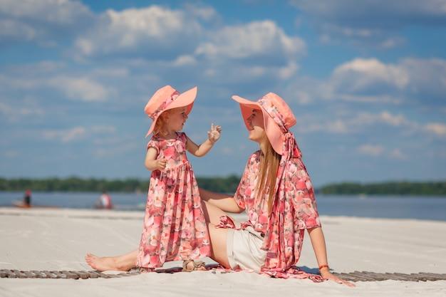 Een klein meisje met haar moeder in bijpassende mooie overgooiers speelt in het zand op het strand. stijlvolle familielook.
