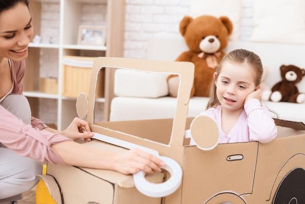 Een klein meisje met haar moeder speelt met een speelgoedauto.