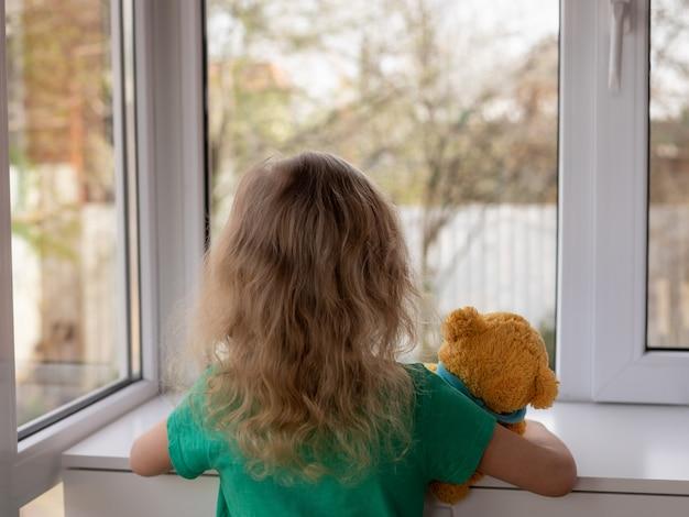 Een klein meisje met haar teddybeer kijkt uit het raam naar de tuin verblijf thuis concept