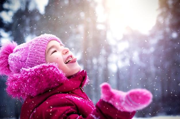 Een klein meisje met haar tong die naar buiten hangt, vangt sneeuwvlokken in de winter in een besneeuwd bos. roze gebreide warme muts. de vreugde en magie van kinderen. ruimte kopiëren