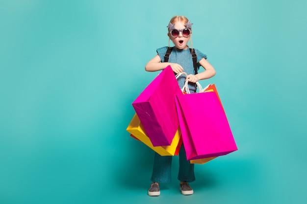 Een klein meisje met kleurrijke tassen