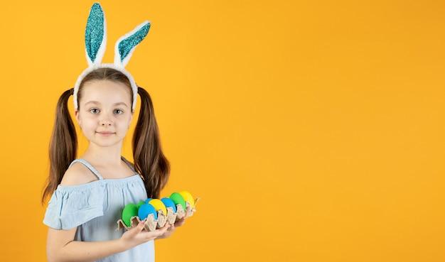 Een klein meisje met konijnenoren op haar hoofd heeft een dienblad met eieren van verschillende kleuren in haar handen