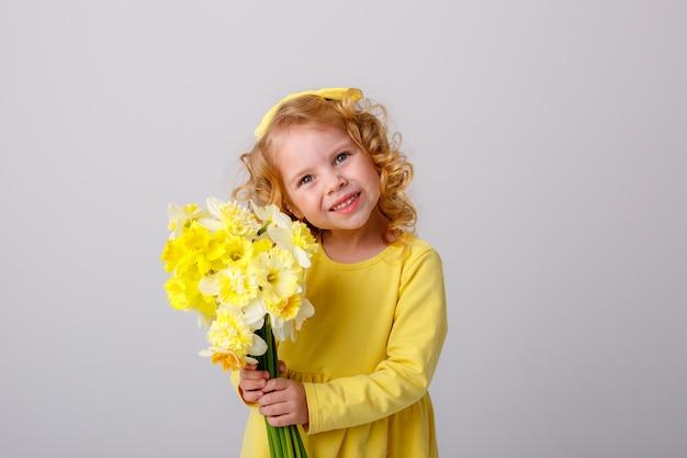 Een klein meisje met krullend haar in een gele jurk met een boeket van lentebloemen op een witte ruimte glimlacht