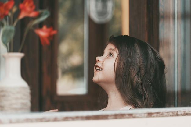 Een klein meisje met lang haar zit aan een tafel in een café en lacht. hoge kwaliteit foto