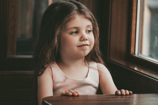 Een klein meisje met lang haar zit aan een tafel in een restaurant en lacht. hoge kwaliteit foto