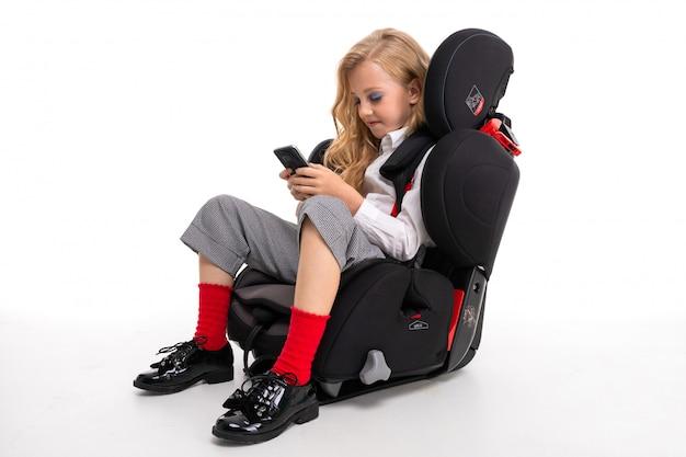 Een klein meisje met make-up en lang blond haar in een wit overhemd, rode pull-ups, broek in een kooi, rode sokken en schoenen in een kinderstoel met telefoon