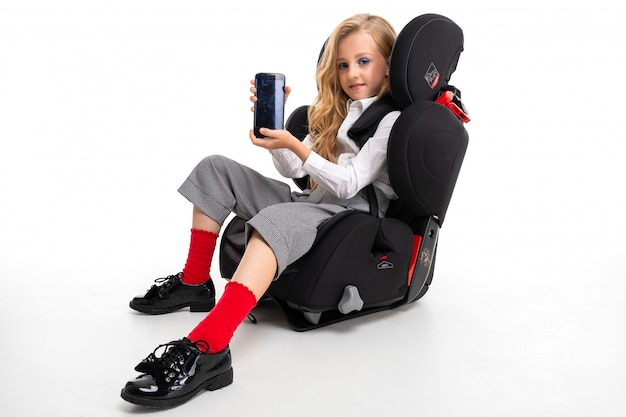 Een klein meisje met make-up en lang blond haar in een wit overhemd, rode pull-ups, broek in een kooi, rode sokken en schoenen met telefoon in een kinderstoel