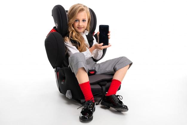 Een klein meisje met make-up en lang blond haar in een wit overhemd, rode pull-ups, broek in een kooi, rode sokken en schoenen met telefoon in een kinderstoel.