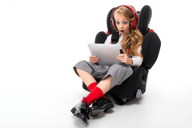 Een klein meisje met make-up en lang blond haar in een wit overhemd, rode pull-ups, een broek in een kooi, rode sokken en laarzen met een tablet en een koptelefoon in een kinderstoel.