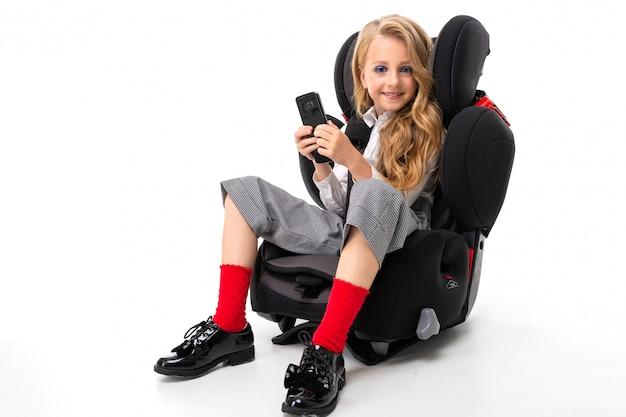 Een klein meisje met make-up en lang blond haar zit in een auto kinderstoel met mobiele telefoon, chatten met vrienden en glimlacht