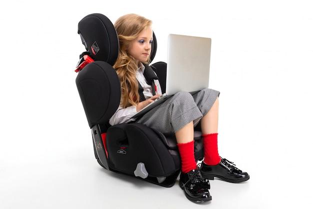 Een klein meisje met make-up en lang blond haar, zittend in een autostoel met laptop, oortelefoons, muziek luisteren en chatten met vrienden