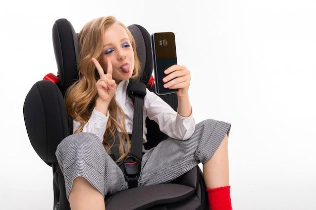 Een klein meisje met make-up en lang blond haar, zittend in een autostoel met mobiele telefoon, doet selfie en toont vrede
