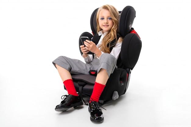 Een klein meisje met make-up en lang blond haar, zittend in een autostoel met mobiele telefoon en chatten met vrienden