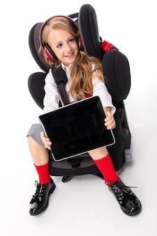 Een klein meisje met make-up en lang blond haar, zittend in een autostoel met tablet, oortelefoons, muziek luisteren en chatten met vrienden