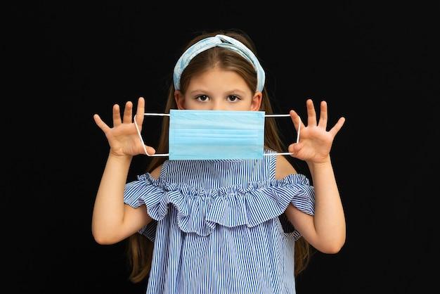 Een klein meisje met medische maskers op een geïsoleerde zwarte achtergrond.