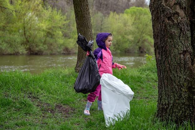 Een klein meisje met meelzakken in het bos helpt bij het opruimen van het afval.