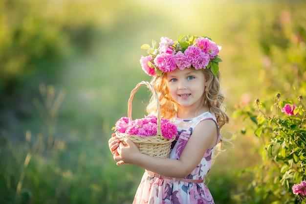 Een klein meisje met mooi lang blond haar, gekleed in een lichte jurk en een krans van echte bloemen op haar hoofd, in de tuin van een theeroos