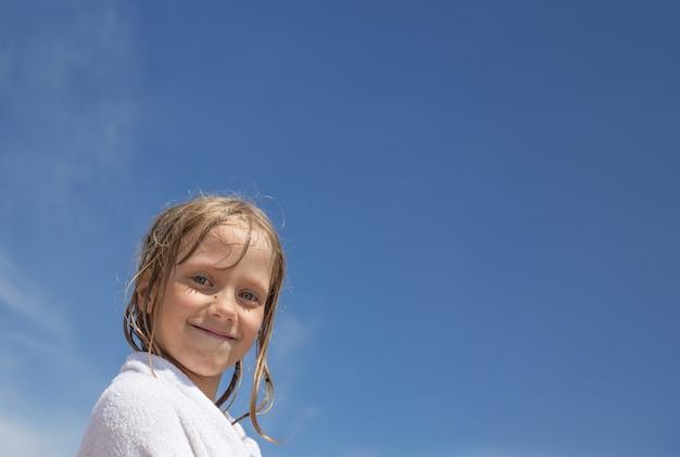 Een klein meisje met nat blond haar, gewikkeld in een witte handdoek, glimlacht tegen de blauwe lucht. zomervakantie op zee. fijne vakantie.