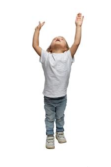 Een klein meisje met opgeheven handen kijkt omhoog. kind 4 jaar oud in spijkerbroek. volledige hoogte. geïsoleerd op een witte achtergrond.