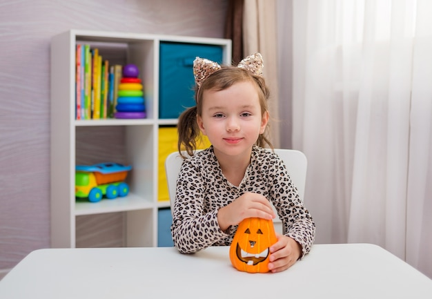Een klein meisje met oren en een oranje pompoen zit aan een tafel in de kamer en glimlacht