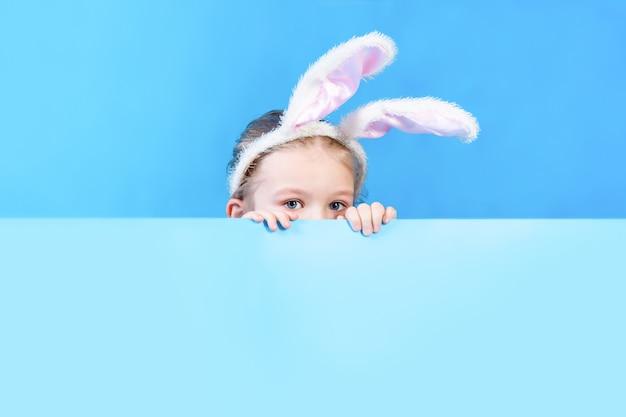 Een klein meisje met oren van een wit konijnenkostuum dat van achter een vel blauw karton gluurt. kopieer ruimte.