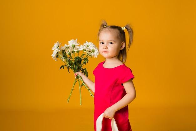 Een klein meisje met paardenstaarten in een rode jurk staat en houdt een boeket witte bloemen op een gele ondergrond met ruimte voor tekst