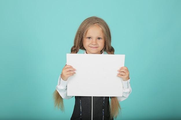 Een klein meisje met paardenstaarten in een wit overhemd en een grijze zomerjurk een schoolmeisje houdt een wit laken vast