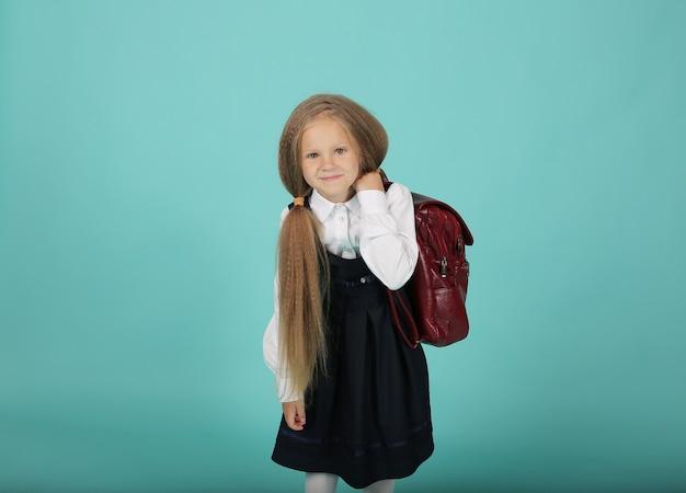 Een klein meisje met paardenstaarten in een wit overhemd en een grijze zomerjurk een schoolmeisje met een rugzak