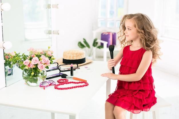 Een klein meisje met rode jurk en cosmetica.
