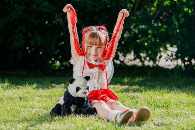 Een klein meisje met rode staartjes zit in de zomer in de natuur met een speelgoedbeerpanda. hoge kwaliteit foto
