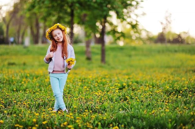 Een klein meisje met rood haar glimlacht tegen een veld van paardebloemen en groen gras. zomer, jeugd, vakantie. ruimte voor tekst, kopie ruimte