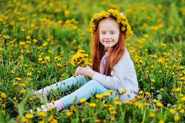 Een klein meisje met rood haar glimlacht tegen een veld van paardebloemen en groen gras. zomer, jeugd, vakantie