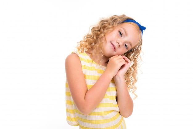 Een klein meisje met rood hoophaar in een wit en geel gestreept zomerpak, met een blauw verband op haar hoofd.
