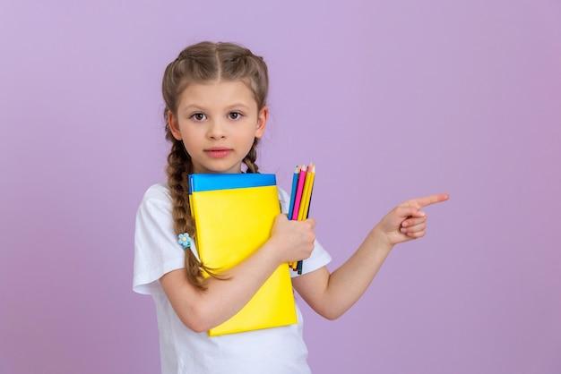 Een klein meisje met staartjes en boeken om te lezen en te bestuderen wijst naar de zijkant.