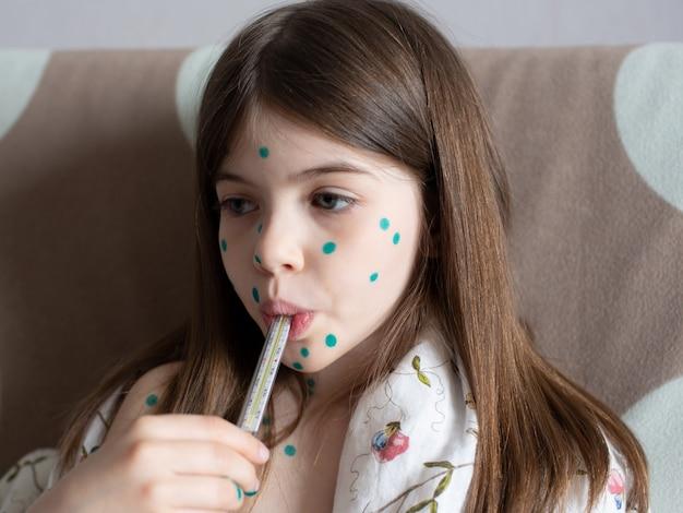 Een klein meisje met waterpokken meet haar temperatuur
